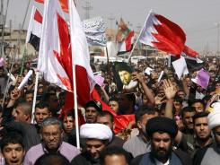 Followers of Shiite cleric Muqtada al-Sadr chant slogans while waving Bahrain flags during a demonstration in Basra, Iraq's second-largest city.