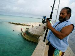 A man fishes on a bridge on Tarawa atoll, Kiribati.
