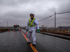 A policeman stands guard at one of the entrances surrounding the Fukushima nuclear plant in Japan.