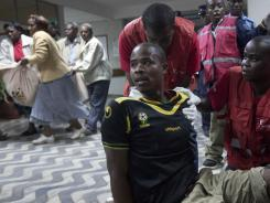 A man injured in Saturday's grenade attack sits on the floor of the Kenyatta Hospital in Kenya, as another wounded individual is carried in a bed sheet, left.