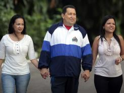 Venezuelan President Hugo Chavez walks holding hands with his daughters Rosa Virginia, left, and Maria Gabriela on Wednesday in Havana.