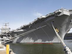 The aircraft carrier USS Enterprise awaits at a pier in Norfolk, Va., while sailors finish preparations in March for the ship's final voyage.