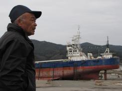 Masaichi Sato, 67, stands in the port city of Kesennuma, in northest Japan, on Friday near the No. 18 Kyotokumaru, a 330-ton fishing boat that was swept inland over half a mile from the harbor by the tsunami on March 11, 2011.