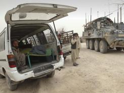 The covered body of a person who was allegedly killed Sunday by a U.S. servicemember is seen inside a minibus in Panjwai, Kandahar province, south of Kabul, Afghanistan.