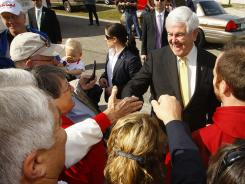 Republican presidential candidate and former House speaker Newt Gingrich, center, campaigns on Saturday outside Mama Lou's restaurant in Robertsdale, Ala.