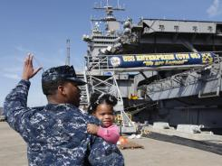 Petty Officer 3rd Class Michael Joseph, carries his daughter Maleah, 1, to his re-enlistment ceremony aboard the nuclear powered aircraft carrier USS Enterprise at the Norfolk Naval Station in Norfolk, Va. on Thursday.