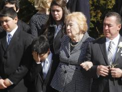 Rosemarie Colvin, second from right, mother of journalist Marie Colvin, watches as her daughter's casket is taken from St. Dominic Roman Catholic Church after her funeral Monday in Oyster Bay, N.Y.