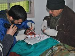 Syrian doctors treat a wounded rebel who was injured by government forces at a makeshift hospital in Homs province.