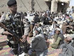 An Afghan security guard watches during Tuesday's prayer ceremony in Panjwai for civilians killed by a U.S. soldier.