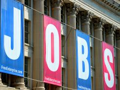 Rising sign: A jobs sign hangs on the U.S. Chamber of Commerce building in Washington, D.C. Last month, employers added 227,000 jobs, the Labor Department said.