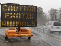 A sign on I-70 near Zanesville, Ohio, warns that exotic animals are on the loose Oct. 19.