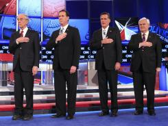 Ron Paul, Rick Santorum, Mitt Romney and Newt Gingrich stand for the anthem during a debate Feb. 22 in Mesa, Ariz. The candidates are turning their attention to Louisiana.