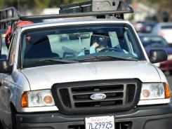 A motorist takes a sip in Long Beach. Feds are weighing use of mobile devices in new guidelines.