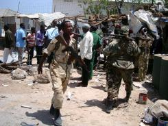 Police and soldiers gather at the site of a suicide blast on Wednesday near the compound of Somali President Sharif Sheikh Ahmed.