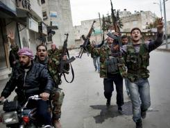Step by step: Rebel fighters cheer Sunday after a Syrian Army tank was destroyed in Idlib.