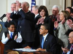 President Obama receives applause after signing the health care overhaul bill into law March 23, 2010, at the White House.