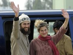 Swiss couple Olivier David Och and Daniela Widmer wave upon their arrival at the Qasim base in Rawalpindi, Pakistan, on Thursday.