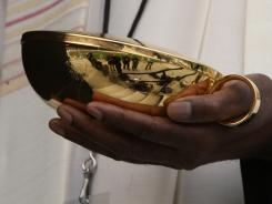 A priest carries communion wafers. A gay woman says she was denied the sacrament at her mother's funeral.