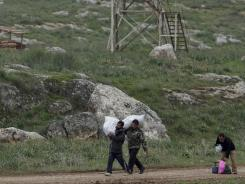 Syrians fleeing violence walk toward the border near Reyhanli, Turkey, Thursday. Turkey said Thursday it was considering the establishment of a buffer zone along its border.