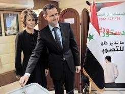 Syrian President Bashar Assad casts his ballot on the now-approved constitution, as his wife, Asma, looks on at a polling station in Damascus, Syria, on Feb. 26.