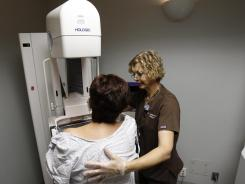 Roxanne Gross, a mammography technologist, conducts a mammogram on a patient in September at UCLA. New health plans provide mammograms.