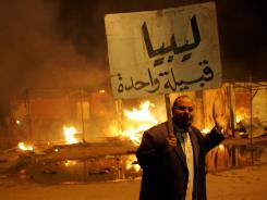 "A Libyan man holds a sign that reads in Arabic, ""Libya is one tribe,"" outside the courthouse in the eastern city of Benghazi."
