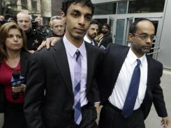 Dharun Ravi, left, is helped by his father, Ravi Pazhani, right, as they leave court Friday in New Brunswick, N.J.