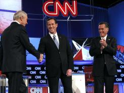 Republican presidential candidates from left, Ron Paul, Rick Santorum and Mitt Romney shake hands prior to a debate.