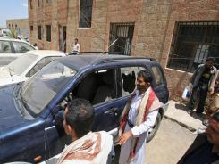 Yemenis gather around a damaged vehicle purported to belong to an American teacher shot by gunmen Sunday in Taiz.