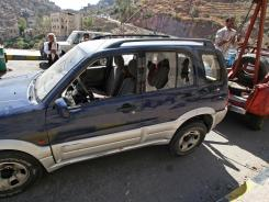 A damaged vehicle said to belong to an American teacher shot by gunmen is towed away Sunday in Taiz, Yemen.