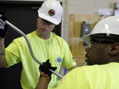 Veterans Leonard Jagla III, left, and Fredrick Moore examine a bend on a piece of conduit during an electrician's training class at Associated Builders and Contractors in Elk Grove Village, Ill.