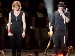 Sugarland duo Jennifer Nettles, left, and Kristian Bush, right, react as they perform on stage.