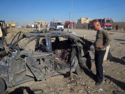 A man stands next to a destroyed vehicle at the scene of a car bomb attack Tuesday in Kirkuk, Iraq.