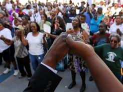 Rev. Glenn Dames leads people in prayer at the Titusville (Fla.) Courthouse on Sunday at a rally demanding justice for Trayvon Martin.