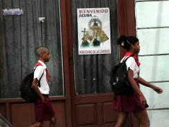 Children walk by a picture of Pope Benedict XVI on Thursday in Santiago de Cuba. He is scheduled to arrive in the country March 26.