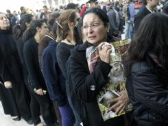 An Egyptian Christian woman carries a poster of the late Pope Shenouda III as others line up to enter his funeral at St. Mark Coptic Orthodox Church in Cairo.