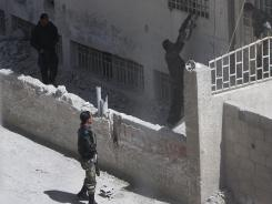 Syrian army soldiers raid a building as they search for rebels Tuesday in a suburb of Damascus.