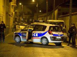 French policemen attempt to arrest a suspected gunman on Wednesday in Toulouse, southwestern France.