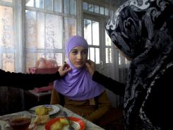 Friends adjust 15-year-old Seda Makhagieva's hijab in her kitchen in Serzhen-Yurt, Chechnya. Seda started wearing the head covering a year ago, despite her mother's disapproval.