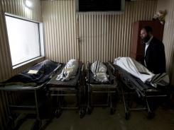 An Israeli Zaka volunteer stands next to the bodies of the shooting victims in a morgue before their funeral in Jerusalem on Wednesday.