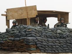 After the massacre of civilians: U.S. Army and Afghan soldiers man a guard tower at the Panjwai district on March 11.