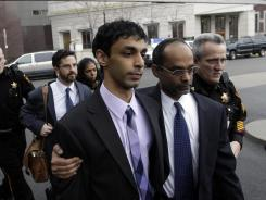 Dharun Ravi, center, is helped by his father, Ravi Pazhani, as they leave court in New Brunswick, N.J., on Friday.
