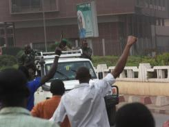 Civilians cheer as mutinous soldiers drive past in Bamako, Mali, on Wednesday.