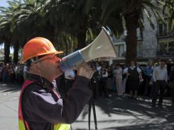 An employee gives instructions to his peers outside a building in Mexico City after an aftershock Thursday.
