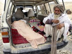 An elderly Afghan man sits next to the covered body of a person who was allegedly killed by a U.S. servicemember, in a minibus in Panjwai, Afghanistan, on March 11.