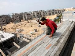 A Palestinian laborer works at a construction site of a residential project funded by the U.N.