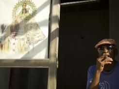 A Cuban man smokes a cigar Sunday next to a poster proclaiming the visit of Pope Benedict XVI.