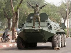 A soldier poses atop a military vehicle guarding the presidential palace Friday following a military coup in Bamako, Mali.