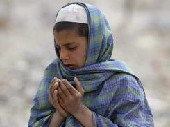 An Afghan boy prays Saturday over the grave of one of the victims of a shooting spree linked to U.S. soldier Robert Bales.