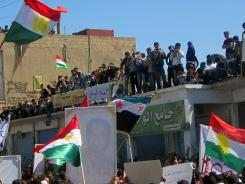 Syrian Kurds march during an anti-regime protest in the city of Qamishli on the border with Turkey on March 23.